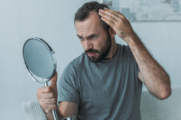 bearded middle aged man with alopecia looking at mirror, hair loss concept Fotobehang