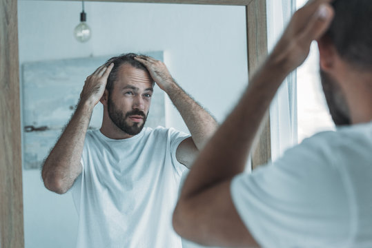 cropped shot of middle aged man with alopecia looking at mirror, hair loss concept
