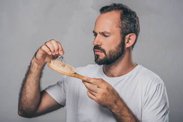 bearded middle aged man holding hairbrush, hair loss concept Fotobehang