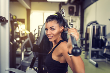 Woman using lat pulldown machine in gym fitness