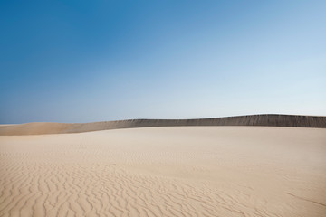 Desert like sand dune with textured sand and bright blue sky