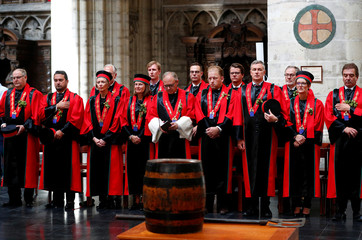 Members of the Knighthood of the Brewer's Paddle attend a mass in front of a barrel of beer at the Saint Gudula Cathedral in Brussels
