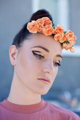 Female model with fresh orange floral headpiece and striking eye makeup.