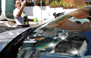 A supporter of presidential candidate Jair Bolsonaro takes a picture as an inflatable doll depicting Bolsonaro is reflected in the glass of a car in front of the Albert Einstein hospital after he was stabbed in Juiz de Fora, in Sao Paulo