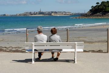 Couple assis sur un banc face à Saint-Malo