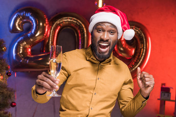 excited african american businessman in santa hat holding glass of champagne at new year corporate party