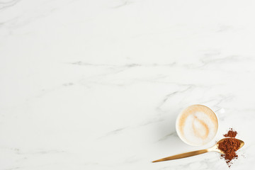 Concept of coffee background. Flat lay of coffee and golden spoon with ground coffee on marble background. Top view with copy space.