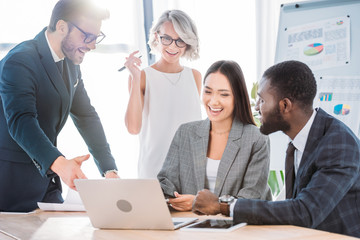 multicultural businesspeople laughing while working on project in office