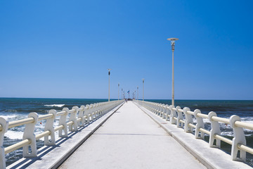 Long pier heading to the sea, in a sunny day with blue sky.