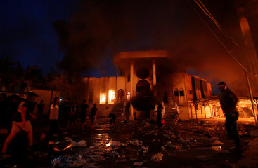 Iraqi protesters are seen in front of the burnt Iranian Consulate in Basra