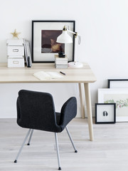 Chair standing near desk and pictures.