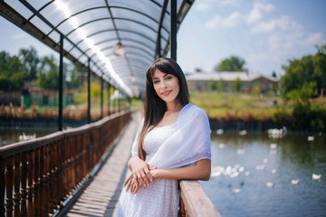 Beautiful girl with black long hair in a white dress on a bridge, walk near a pond. An orthodox woman