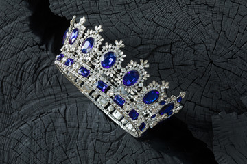 silver royal crown on a black wooden background