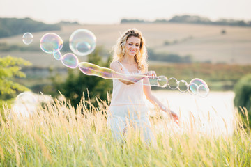 Girl doing soap show at sunset. Original genre. Large soap bubbles