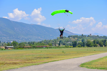 paratrooper with green parachute prepares for landing. On background the blue sky, mountains and green hills