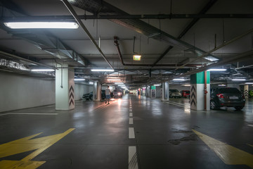 Large hall with columns of underground car parking garage with many automobiles in modern mall or shopping center
