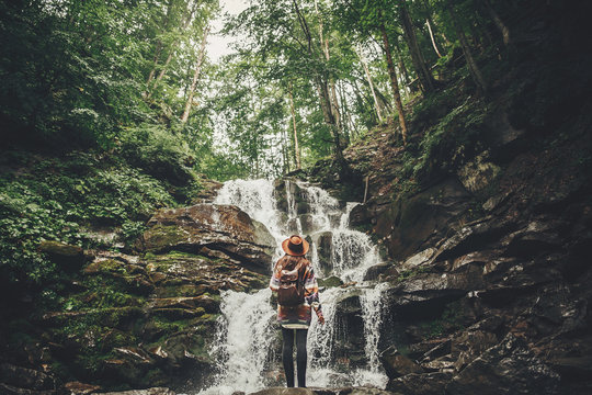 stylish hipster girl in hat with backpack looking at waterfall in forest in mountains. traveler woman exploring woods. travel and wanderlust concept. summer vacation, space for text
