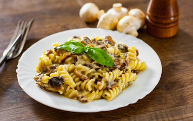 fusilli pasta with mushroom and cream sauce in white plate on a wooden background