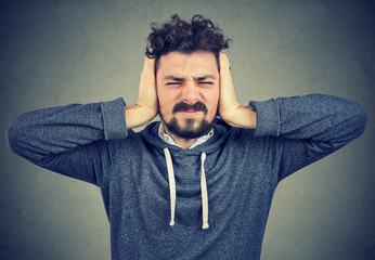 Stressed man squeezing head with hands