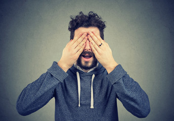 man covering his eyes with hands over gray background