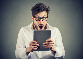 Man with tablet looking shocked