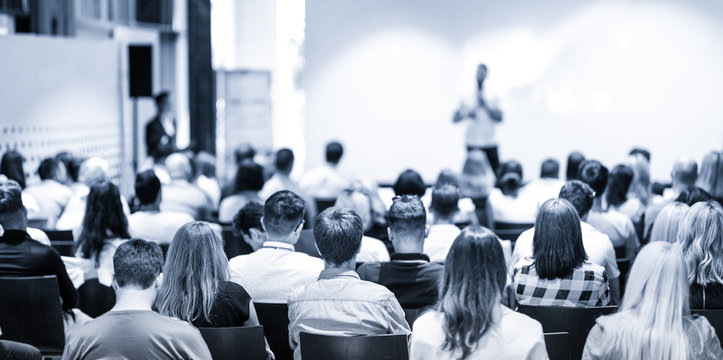 Speaker giving a talk in conference hall at business event. Focus on unrecognizable people in audience. Business and Entrepreneurship concept. Blue toned greyscale image.