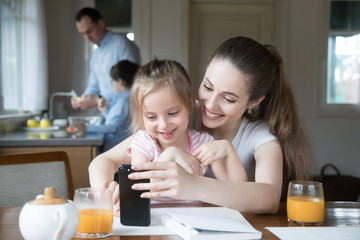 Happy mother and daughter having fun playing game on smartphone in kitchen, mom and girl spending time together watching cartoons or children video on phone, parent teach little kid using cell