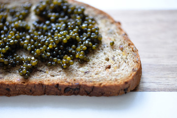 Slice of rye black bread with black sturgeon caviar on a wooden cutting board closely. Elegant macro photo with expensive luxury delicatessen snack for design, party, banners, cafe, shop, advertising