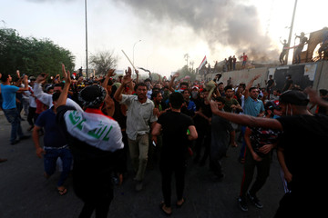 Iraqi protesters shout slogans during an anti-government protest near the burnt building of the government office in Basra