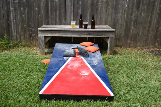 Red, white and blue corn hole game in back yard with dusty bags landing on board