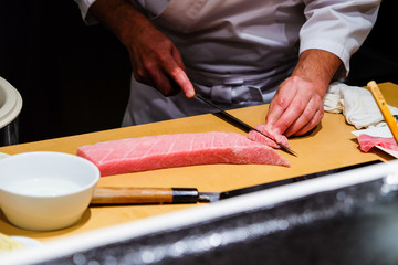A chef skillfully prepares fresh raw fatty tuna for his customers.