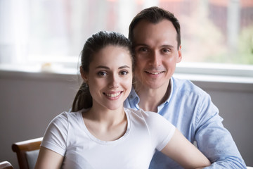 Portrait of smiling boyfriend and girlfriend hugging looking at camera, happy millennial couple embrace posing for photoshoot, middle aged man hold young woman in arms making picture together