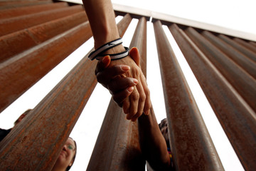 "People shake hands through the border fence during the ""Interfaith Service for Justice and Mercy at the Border"" to demand the U.S. government to end the separation of immigrant children from their parents at the border, in Ciudad Juarez"