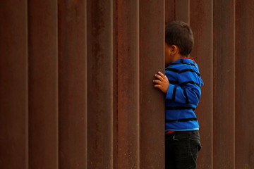 "A child peeks through the border fence during ""Interfaith Service for Justice and Mercy at the Border"" to demand the U.S. government to end the separation of immigrant children from their parents at the border, in Ciudad Juarez"