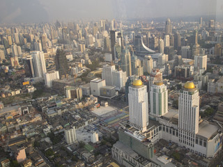 View of Bangkok from above, photo through the window, sunset background
