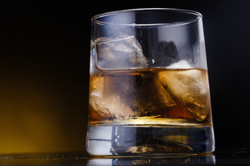 a glass with whiskey and ice on a background