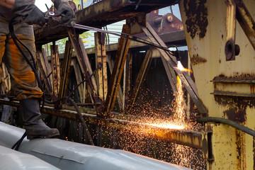 Cutting metal with a gas burner.