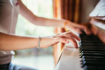 Junges Mädchen spielt leidenschaftlich auf Klavier, Ausschnitt der Hände