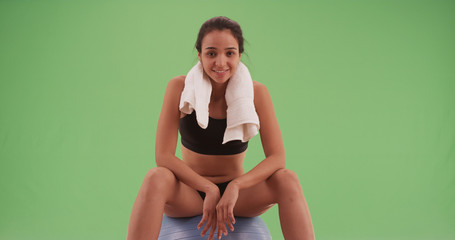 Latina woman sitting on a yoga ball and staring at the camera on green screen
