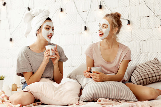 Portrait of beautiful smiling girls with cosmetic cleansing masks sitting in bed drinking hot coffee and having open dialogue. Cozy atmosphere and lovely interior in light colours