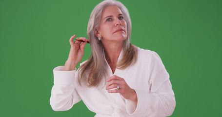 Portrait of senior caucasian woman combing healthy hair on greenscreen