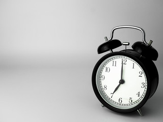 Alarm Clock isolated on white, in black with shadow, showing seven o'clock