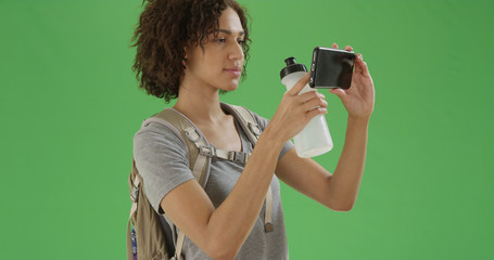 Millennial african American girl takes a picture with her phone on green screen