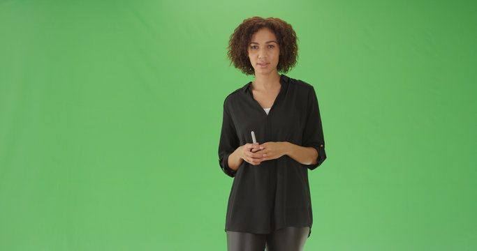 Young black female teacher explaining lesson to class on green screen