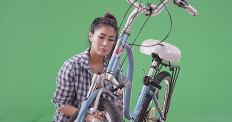 Asian woman fixing her bicycle on green screen