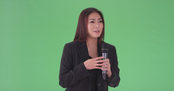 Asian millennial businesswoman speaking through microphone on green screen