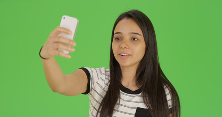 Cute female teen takes a selfie with phone on green screen