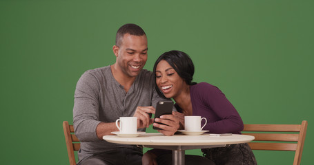 Black couple watching a video on phone while sitting at a cafe on green screen