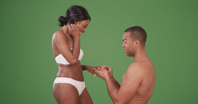 Man proposing to fiancee in their swimwear on green screen