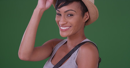 Black woman in tank top and sun hat smiling on green screen